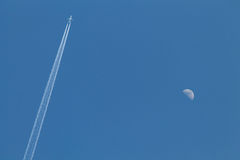 Airplane and moon. Image of an airplane passing by the moon in the blue sky royalty free stock images