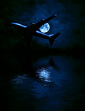 Airplane and the moon over the sea Stock Photography