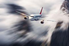 Airplane in motion. Aircraft with motion blur effect is flying in clouds against mountains. Passenger airplane royalty free stock images