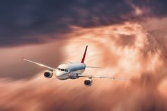 Airplane with motion blur effect is flying in big orange clouds Stock Photo