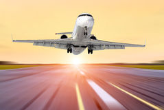 Airplane in motion take off the evening sky sunset sunrise sun airport Royalty Free Stock Photos
