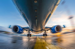 Airplane in motion during takeoff and landing, on a background of sunset and wet runway Royalty Free Stock Photos