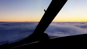 Airplane moves above the cloudness sky on sunset.Camera in cabin of pilot stock footage