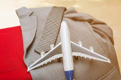 Airplane with necktie and suit on red suitcase, business travel. Concept royalty free stock photos