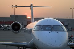 Airplane Nose Sunset. View of an airplane at the gate during sunset royalty free stock photo