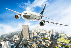 Airplane over cityscape Stock Photography