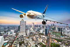 Airplane over cityscape Royalty Free Stock Image