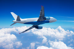 Airplane over the clouds stock images