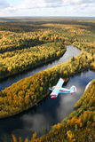 Airplane over forest. The Siberia. The Autumn Taiga. The little airplane fly over forest.  The river flows adown under airplane Royalty Free Stock Photo