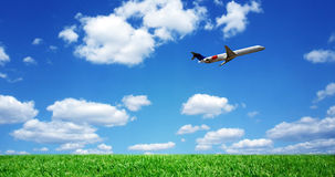 Airplane over grassy field Stock Photo