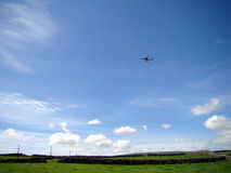 Airplane over green fields. Blue sky and airplane over green fields Royalty Free Stock Photography