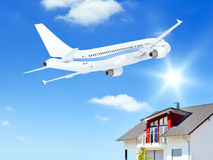 Airplane over house Stock Photography
