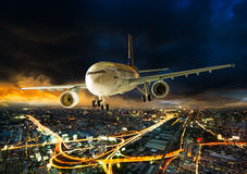 Airplane over night scene city. Airplane for transportation flying over the night scene city on beautiful sunset background Stock Image