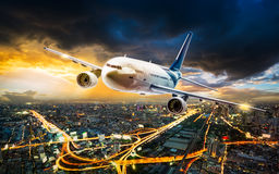 Airplane over night scene city. Airplane for transportation flying over the night cityscape on storm cloud in sunset time Stock Images