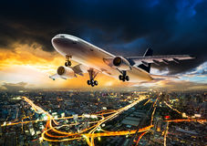 Airplane over night scene city. Airplane for transportation flying over the night cityscape on storm cloud in sunset time Royalty Free Stock Images