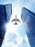 Airplane over office building. Royalty Free Stock Photo