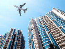 Airplane over office building. Royalty Free Stock Image