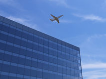 Airplane over office building. Airplane flying over office building Royalty Free Stock Photo