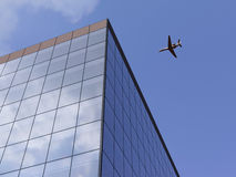 Airplane over office building. Airplane flying over office building Stock Image
