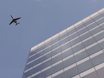 Airplane over office building. Airplane flying over office building Stock Images