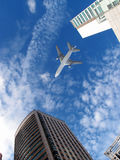 Airplane over office buildings. A airplane flies over modern office buildings Stock Image