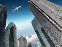 Airplane over office buildings. A airplane flies over modern office buildings Royalty Free Stock Image