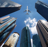 Airplane over office buildings. A airplane flies over modern office buildings Stock Photos