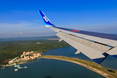 Air Travel. Theme: Airplane Wing against a Vivid Blue Sky and Ocean Royalty Free Stock Photography