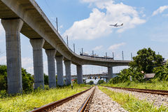 Airplane over skytrain and train. Near airport Royalty Free Stock Photography