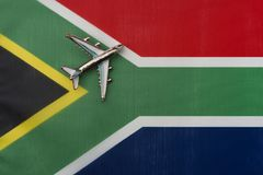 Airplane over South African flag travel and tourism concept. Toy plane on the flag in the background royalty free stock image