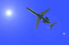 Airplane over the sun flare Royalty Free Stock Photo
