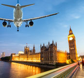 Airplane over Westminster Palace at dusk Stock Photo