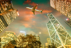 Airplane overflying Hong Kong financial district Stock Photos