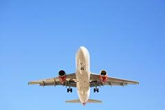 Airplane overhead against blue sky. Airplane flying overhead against a clear blue sky Stock Images