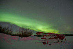 Airplane Parked in Snow Under Northern Lights Stock Photo
