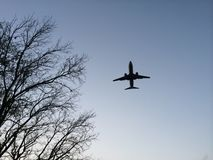 Airplane. Pass through in sunset Stock Photo