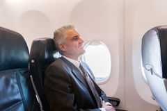 Airplane passenger relaxing. Happy middle aged airplane passenger relaxing during flight on air plane Royalty Free Stock Photo