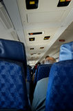 Airplane Passenger View. A shot of inside an airplane cabin seating arrangement.  Focal point is along the same plane as the exit sign with no recognizable faces Stock Photo