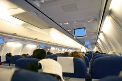 Airplane with passengers interior view Stock Photos