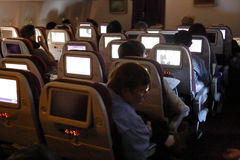 Airplane passengers watch TV on the way from Los Angeles to Seoul South Korea - November 2013 Stock Image