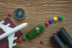 Airplane, passport, compass, binoculars and miniature car on woo Royalty Free Stock Image