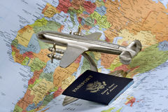 Airplane, passport and map. A vintage model four propeller plane and US passport with map of Europe and Africa in background Stock Photos