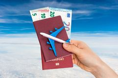 Airplane, passport and money in female hand - travelling concept stock photography