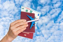 Airplane, passport and money in female hand - travelling concept Royalty Free Stock Photography