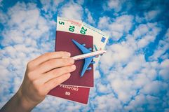 Airplane, passport and money in female hand - travelling concept royalty free stock image