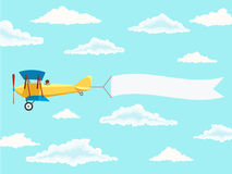 Airplane with pilot and advertising banner in the cloudy sky Royalty Free Stock Photo
