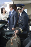 Airplane Pilot Keeping Luggage In Car. With business people in the background at airfield Stock Images