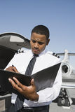 An Airplane Pilot Taking Notes At Airfield Royalty Free Stock Photography