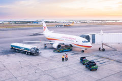 Airplane on platform. Image of an airplane on the airport platform preparing for the next flight. Fuel and luggage truck has arrived, passengers ar boarding Stock Images