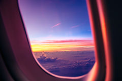 Airplane porthole at sunrise Stock Photos